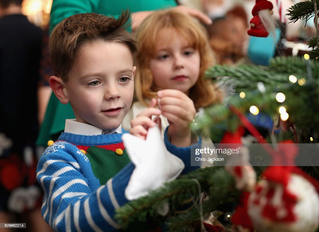 Ronnie Edwards (aged 6) from Cambridge decorates the Clarence House Christmas Tree as Millie Fagan-Barnes (aged 7) looks on at Clarence House on December 14, 2016 in London, England. The Duchess of Cornwall, Patron, Helen & Douglas House invited children from the charity and children supported by Roald Dahl's Marvellous Children's Charity to decorate the Christmas tree and join Her Royal Highness for lunch at Clarence House.