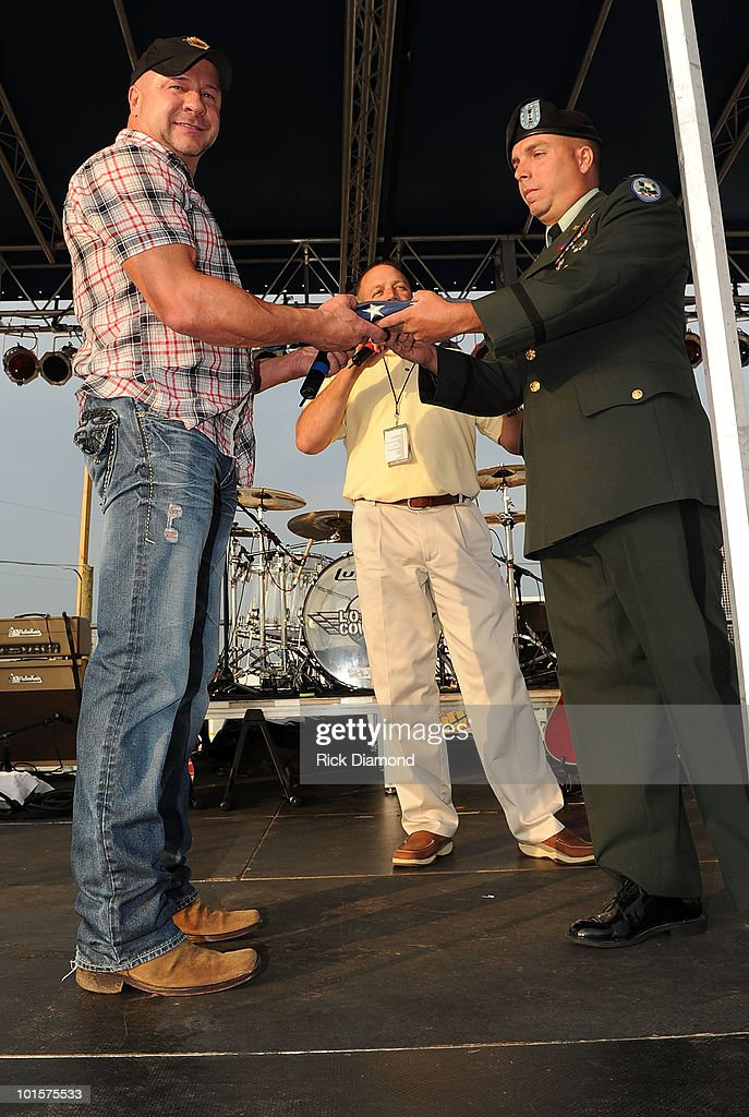 Ronnie Gilley producer of BamaJam is presented a American Flag from Sgt. First Class Mark Johns and Chief Warren Officer Carl Greenwell in front of the crowd attending a VIP welcome event prior to the 2010 BamaJam Music & Arts Festival at the Corner of Hwy 167 and County Road 156 on June 2, 2010 in Enterprise, Alabama.