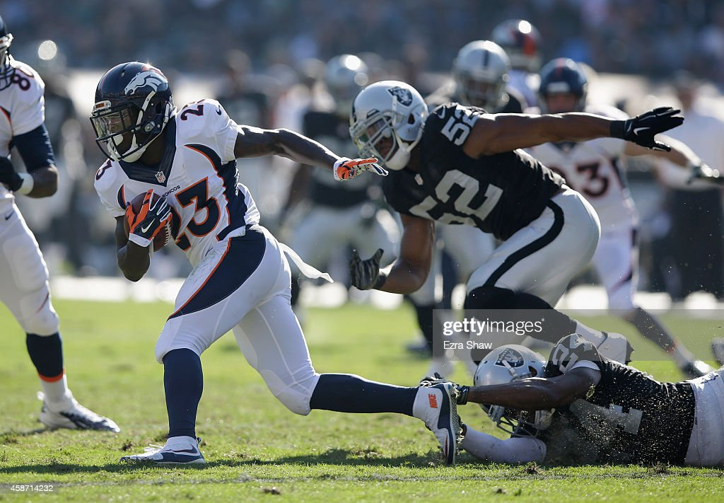 Ronnie Hillman of the Denver Broncos breaks free from Khalil Mack of the Oakland Raiders in the first half at Oco Coliseum on November 9 2014 in...