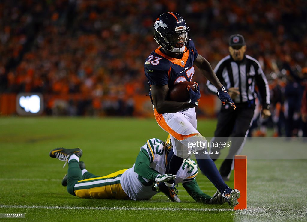 Ronnie Hillman of the Denver Broncos runs in a touchdown against Micah Hyde of the Green Bay Packers in the second quarter at Sports Authority Field...