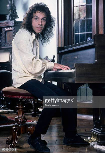 Ronnie James Dio portrait at home sitting at a piano United States July 1987
