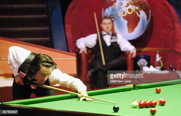 Ronnie O'Sullivan in action as Stephen Hendry looks on during the Embassy World Snooker Semi Final match between Stephen Hendry and Ronnie O'Sullivan...