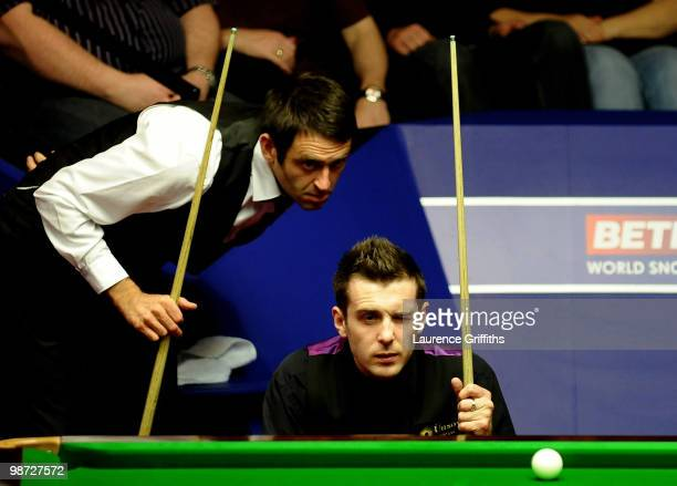 Ronnie O'Sullivan of England and Mark Selby of England show interest as Referee Leo Scullion replaces the balls after a foul shot during their...