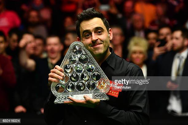 Ronnie O'Sullivan of England celebrates with the Paul Hunter Trophy following victory during the final match against Joe Perry of England on day...