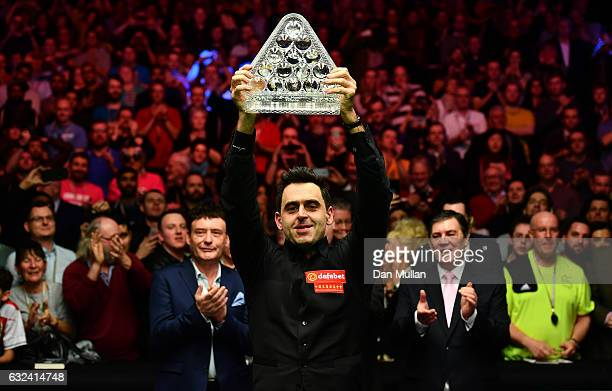 Ronnie O'Sullivan of England lifts the Paul Hunter Trophy following victory during the final match against Joe Perry of England on day eight of the...