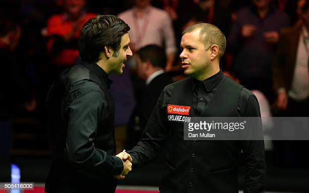 Ronnie O'Sullivan of England shakes hands with Barry Hawkins after defeating him in the final match during Day Eight of The Dafabet Masters at...