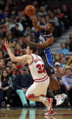 Ronnie Price of the Orlando Magic passes over Jimmer Fredette of the Chicago Bulls at the United Center on April 14 2014 in Chicago Illinois The...