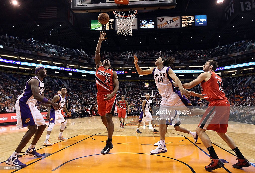 Ronnie Price #24 of the Portland Trail Blazers lays up a shot past Luis Scola #14 of the Phoenix Suns during the NBA game at US Airways Center on November 21, 2012 in Phoenix, Arizona. The Suns defeated the Trail Blazers 114-87.