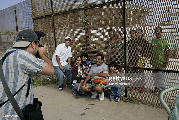 Ronnie Revoredo photographs a family at the US/Mexico border wall on June 10 2007 in San Ysidro California President Bush will meet with key Senators...