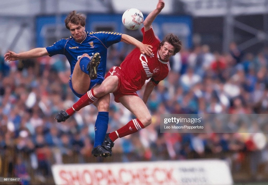 Ronnie Whelan of Liverpool and Detzi Kruszynski of Wimbledon leap in the air to fight for the ball during a first division game between Wimbledon and...