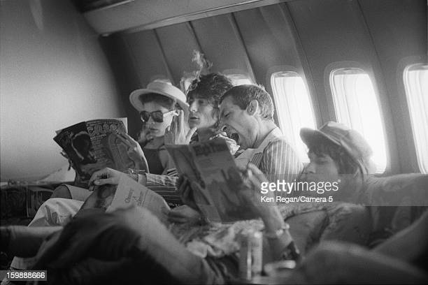 Ronnie Wood Charlie Watts and Keith Richards of the Rolling Stones with Bianca Jagger are photographed reading on their plane in 1975 in Kansas City...