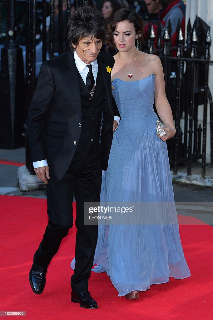 Ronnie Wood (L) of British rock band The Rolling Stones arrives with his wife Sally Humphreys (R) to attend the inaugural Tusk Conservation Awards at The Royal Society in London on September 12, 2013. Britain's Prince William, patron of Tusk and his wife Catherine, Duchess of Cambridge attended the awards that celebrate achievement in the field of African conservation.