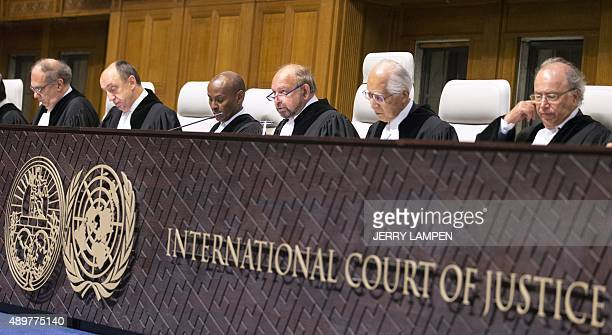 Ronny Abraham French president of the International Court of Justice sits with judges at the ICJ at the Hague on September 24 to deliver the court's...