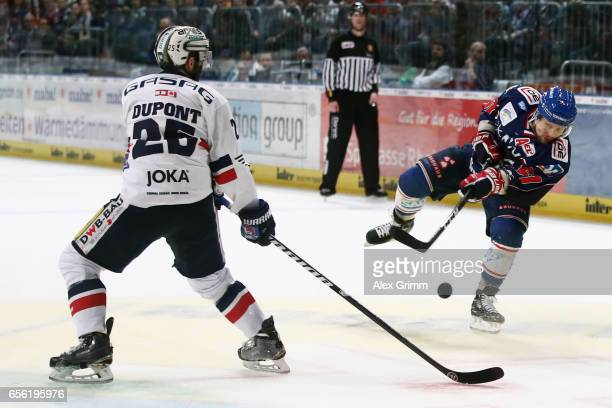 Ronny Arendt of Mannheim takes a shot against Micki DuPont of Berlin during the DEL Playoffs quarter finals Game 7 between Adler Mannheim and...