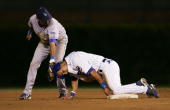 Ronny Cedeno of the Chicago Cubs arrives safe after stealing second as Oscar Robles of the Los Angeles Dodgers tries to tag him on the head in the...
