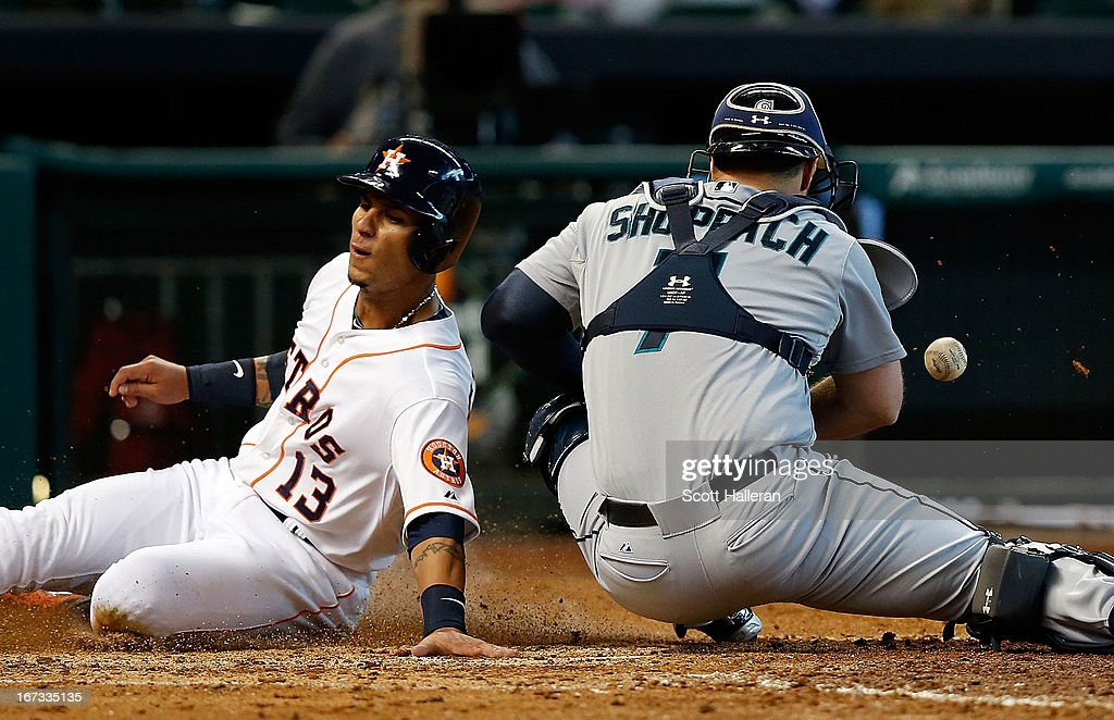 Ronny Cedeno of the Houston Astros slides into home plate under the tag of Kelly Shoppach of the Seattle Mariners in the sixth inning at Minute Maid...