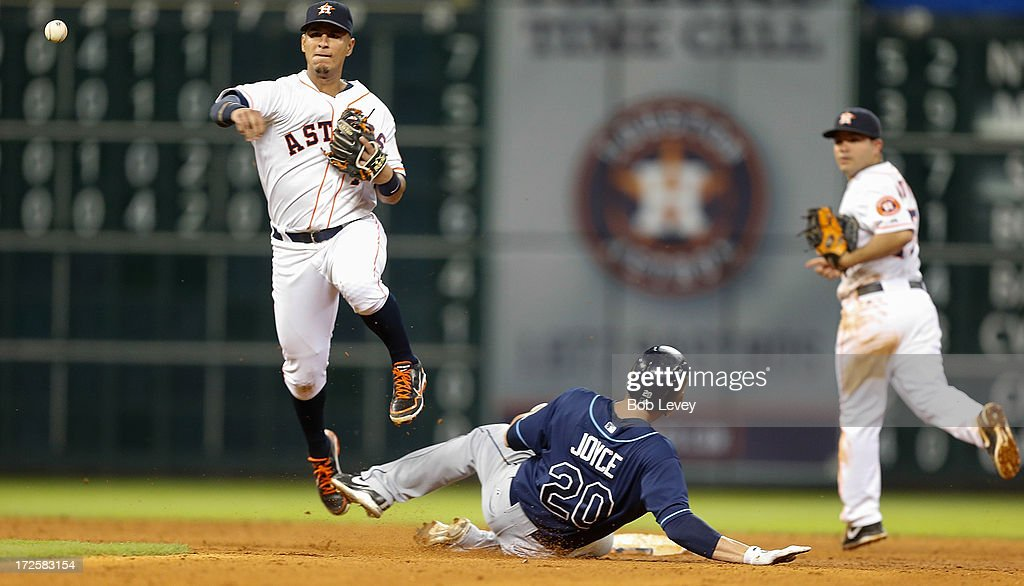Ronny Cedeno #13 of the Houston Astros turns a double play as Matt Joyce #20 of the Tampa Bay Rays attempts to break up the play in the eighth inning at Minute Maid Park on July 3, 2013 in Houston, Texas.