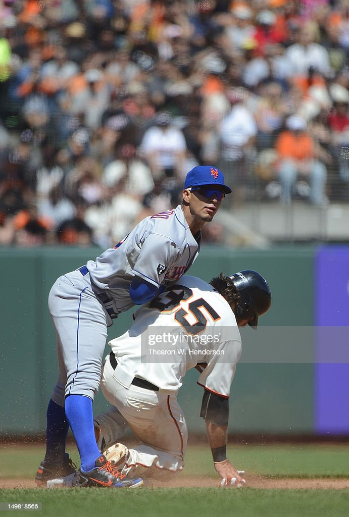 Ronny Cedeno of the New York Mets gets his throw off to complete the doubleplay while avoiding the slides of Brandon Crawford of the San Francisco...