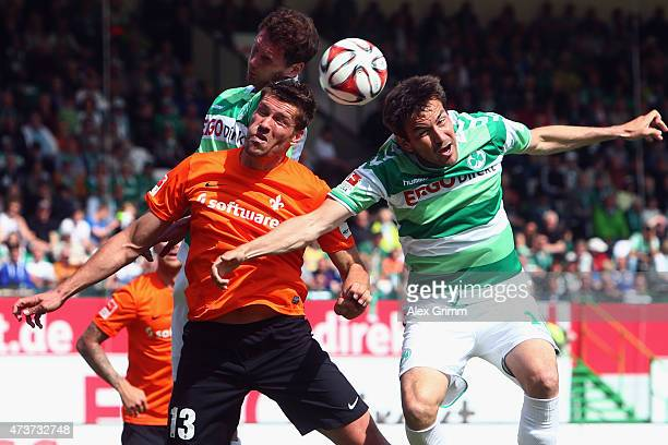 Ronny Koenig of Darmstadt jumps for a header with Goran Sukalo and Benedikt Roecker of Greuther Fuerth during the Second Bundesliga match between...