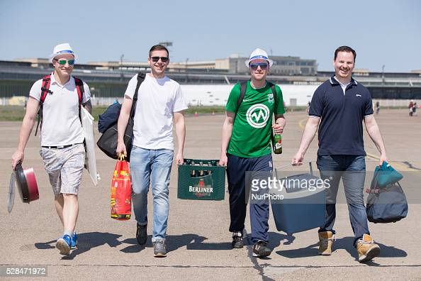 Ronny Norman Daniel and David from Berlin carry a box of beer of the label 'Berliner Pilsner' in the Tempelhofer Feld park during Father's Day or...