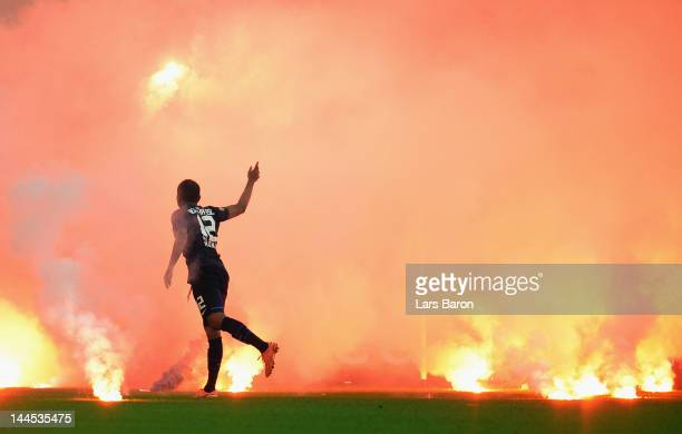 Ronny of Berlin throws flares from the pitch during the Bundesliga Relegation second leg match between Fortuna Duesseldorf and Hertha BSC Berlin at...