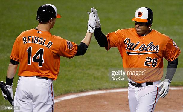 Ronny Paulino of the Baltimore Orioles celebrates with teammate Nolan Reimold of the Baltimore Orioles aftere scoriong a run against the Minnesota...