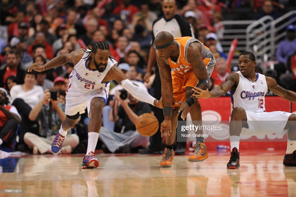 Ronny Turiaf #21 of the Los Angeles Clippers takes a swipe at a loose ball against Jermaine O'Neal #20 of the Phoenix Suns at Staples Center on December 8, 2012 in Los Angeles, California.
