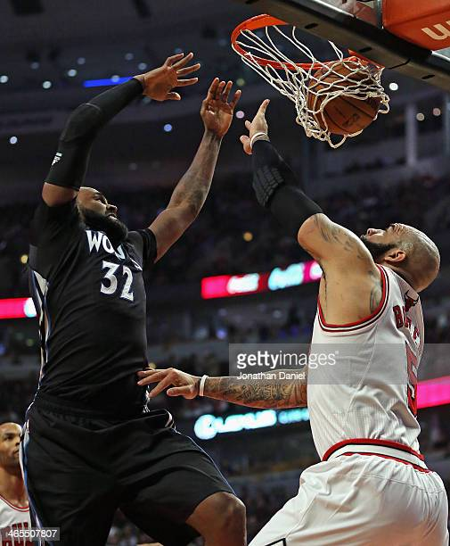 Ronny Turiaf of the Minnesota Timberwolves dunks over Carlos Boozer of the Chicago Bulls at the United Center on January 27 2014 in Chicago Illinois...