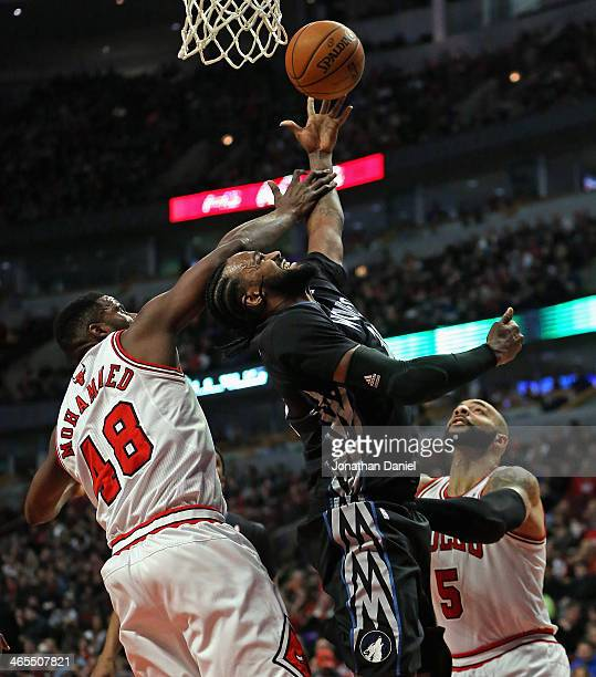 Ronny Turiaf of the Minnesota Timberwolves is fouled by Nazr Mohammed of the Chicago Bulls as he tries to shoot over Carlos Boozer at the United...