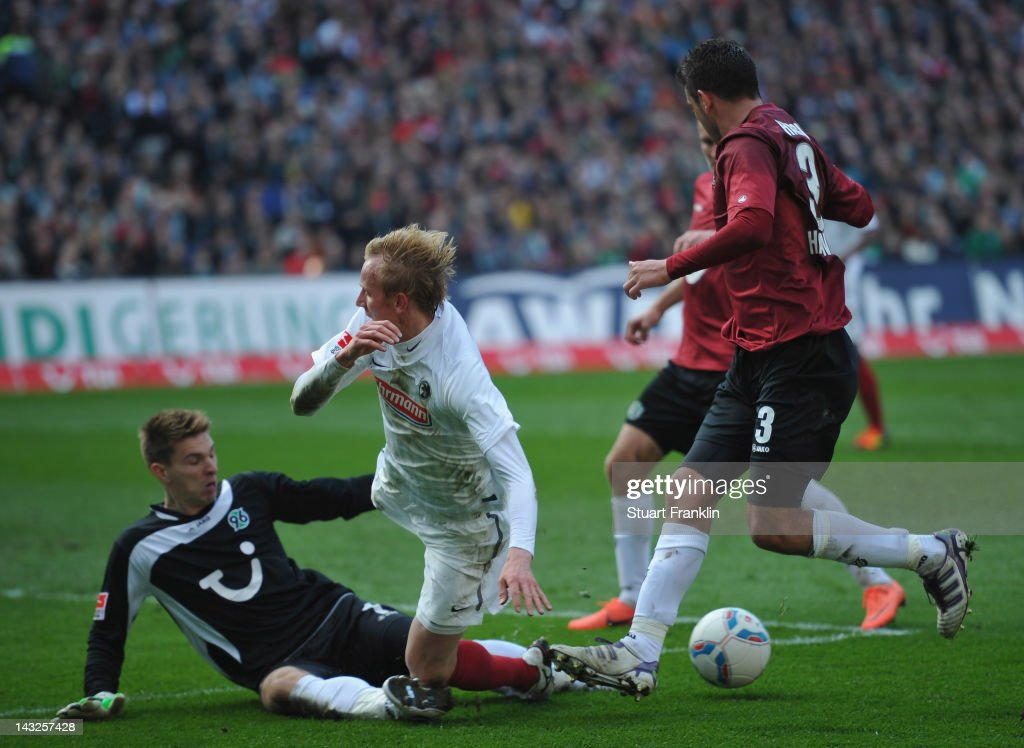 <a gi-track='captionPersonalityLinkClicked' href=/galleries/search?phrase=Ron-Robert+Zieler&family=editorial&specificpeople=727037 ng-click='$event.stopPropagation()'>Ron-Robert Zieler</a> of Hanover makes a save from <a gi-track='captionPersonalityLinkClicked' href=/galleries/search?phrase=Jan+Rosenthal&family=editorial&specificpeople=758564 ng-click='$event.stopPropagation()'>Jan Rosenthal</a> of Freiburg during the Bundesliga match between Hannover 96 and SC Freiburg at AWD Arena on April 22, 2012 in Hannover, Germany.