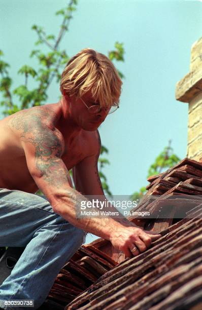 A roof tiler fits the slates to the roof of the Marie Curie Cancer Care show garden designed by Patrick Mccann Garden Design during the build up to...