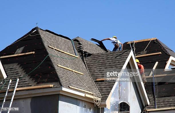 Trabalhadores em cima do telhado de casa com céu azul