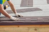 Roofer builder worker installing roof shingles.
