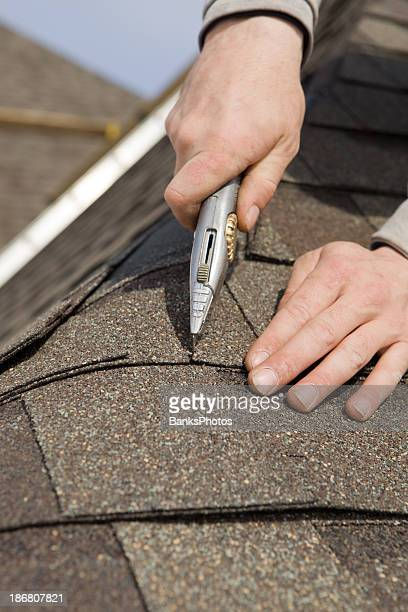 Roofer Trimming a New Shingle on Home Construction Project