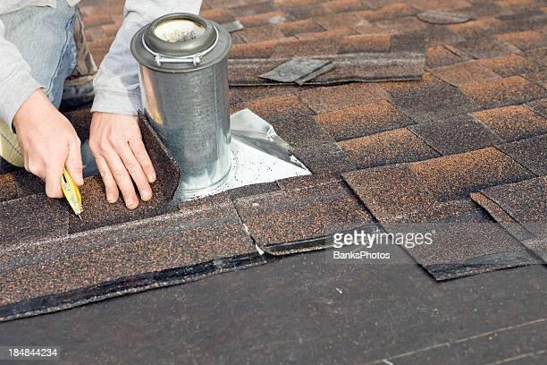 Roofer Trimming Shingle around Plumbing Vent Flashing