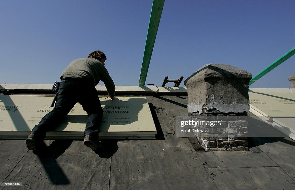 A roofer works on insulation material during a renovation to optimize the thermal insulation of a roof on March 28, 2007 in Frankfurt, Germany. Germany is pursuing aggressive policies in an effort to stem global warming.