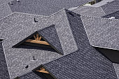 Rooftop in a newly constructed subdivision showing asphalt shingles and multiple roof lines