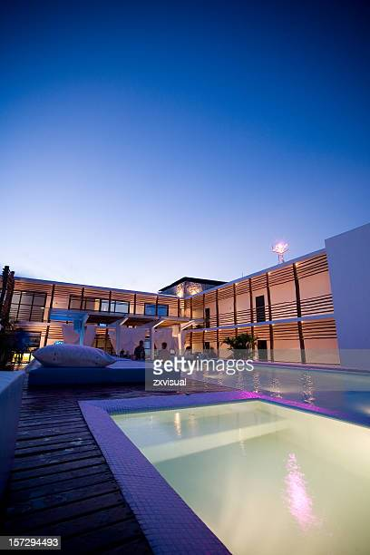 A rooftop lounge at night with a pool