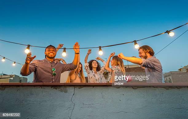 Rooftop party scene, dancing