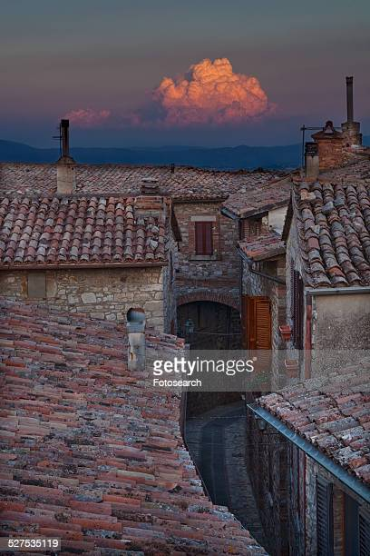 Rooftop view of Italian village street with houses and roof tiles in foreground and spectacular sunset and hills beyond