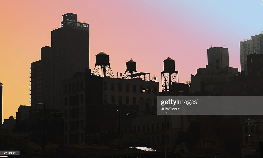 Rooftops with water tanks in silhouette against colorful sky