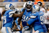 Rookie Ezekiel Ansah of the Detroit Lions celebrates with teammates Willie Young and Nick Fairley while playing the Chicago Bears at Ford Field on...