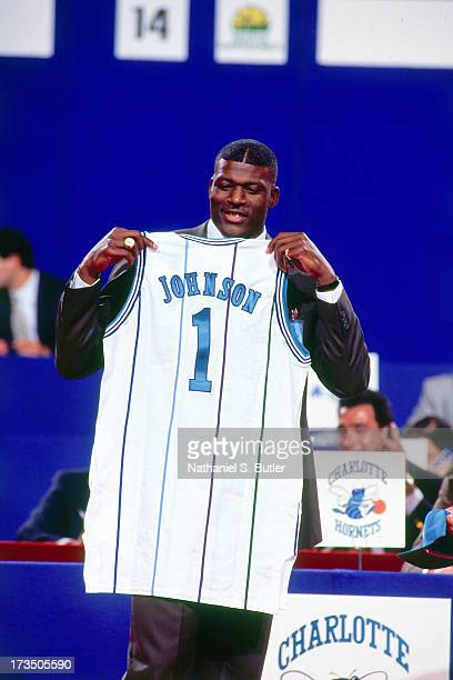 Rookie Larry Johnson of the Charlotte Hornets holds up a jersey after being picked first overall during the 1991 NBA Draft at Madison Square Garden...
