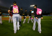 Rookie Pittsburgh Pirates pitchers wear children's backpacks in a hazing traditon as they head to the bullpen before the game with the Los Angeles...