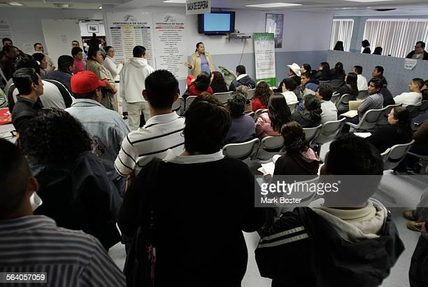 –A room full of people wait for health care information at the Mexican Consulate in Santa Ana No one is feeling the impact of the increasing number...