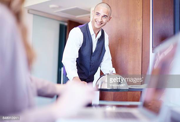 Room service for businesswoman working on laptop in hotel room