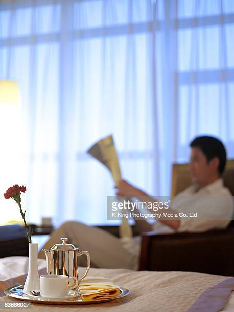 Room service tray, man reading newspaper