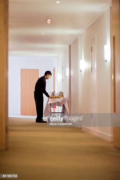 Room service waiter by cart in hotel corridor