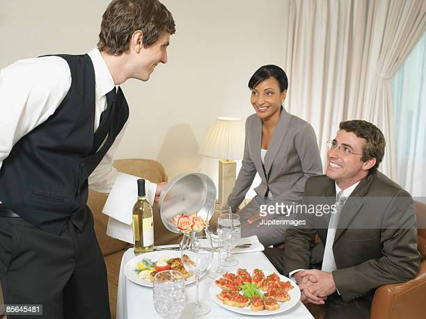 Room service waiter serving food to couple