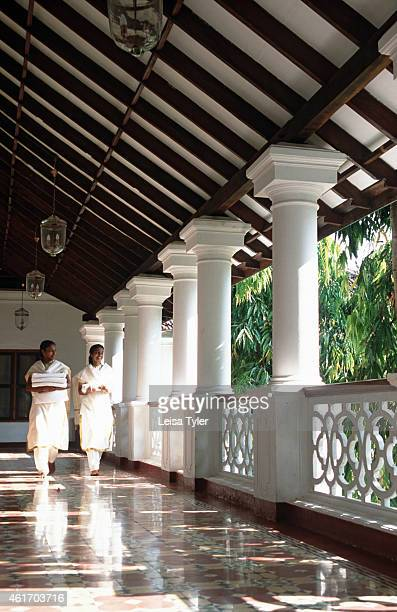 Room staff walking through the corridors of Kalari Kovilakom a 19th century palace in the hills above Palakkad Kerala recently converted into an...